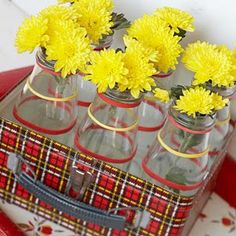 centerpiece: old lunch box, vintage glass milk jars, colored rubberbands & flowers thestylesisters.blogspot.com