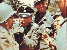 Un grupo de soldados de las Waffen-SS interrogando a un americano capturado. El SS-Sturmbannführer (mayor) está hablando enérgicamente al capturado mientras el otro parece divertido por la situación