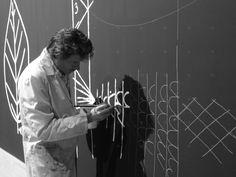 """l'arch. Federico Lardera dipinge la parete della mostra con alcuni disegni di Klee tratti dalle lezioni Bauhaus e raccolti in """"teoria della forma e della figurazione""""."""