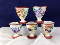 A delightful set of 5 vintage Porcelain Egg Cups! Each has coordinating painted colors and a grape/berry/floral motif. These are handpainted and each is signed by the artist--see photo of egg cup in hand. This lovely set is in excellent vintage condition.  gidgetsvintagefinds.com