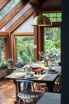A brass pendant light over the farm table adds a modern touch to this cottage-style sun room. Photo by Heidi's Bridge.
