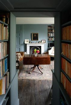 Dark wood floor, lots of books, dark teal walls, light
