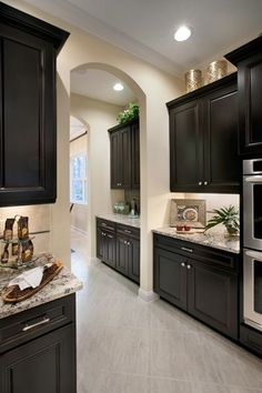 Kitchen: Dark Cabinets, Light Walls, Granite, Stainless Steel And Tile  Flooring