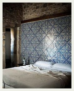 I love the use of these tiles as headboard for an otherwise stark bedroom. Pretty cool idea for a shabby-chic / rustic bedroom