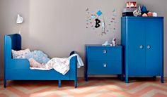 ブルーの伸長式ベッドと引き出し付きチェスト、ワードローブがある子供部屋