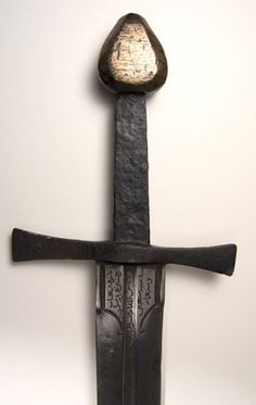 This 14th century European war sword was probably captured from a crusader and taken as a trophy to the arsenal at Alexandria. It is a typical Knightly sword of the period. The crossguard is of steel and the drop-shaped pommel of brass. (The pommel is likely to be a replacement). The blade is two-edged and bears an inscription in Arabic just below the crossguard.