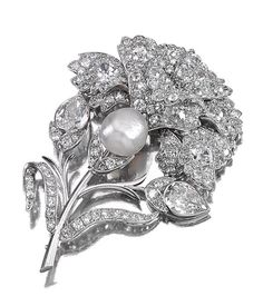 PEARL AND DIAMOND BROOCH, 1930S.  Designed as a stylised flower, the central pearl within surrounds of circular- and single-cut, cushion- and pear-shaped diamonds.