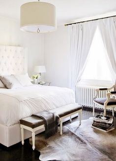 Love this bedroom / cowhide rug / white upholstered headboard