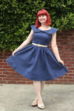 Petite 5 foot girl wearing a Lindy Bop Hetty swing dress in navy blue polka dots with off white accessories.