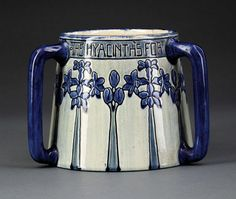 """A Newcomb College Art Pottery High Glaze Tyg, 1903, decorated by Mazie T. Ryan with hyacinth and the text """"The Hyacinth's for Constancy with its Unchanging Blue"""", incised and glazed with dark blue, base marked with Newcomb cipher, decorator's mark, Joseph Meyer's potter's mark, reg. no. Y78, and """"U"""" for white clay body, height 5 3/4 in. Note: Repaired break"""
