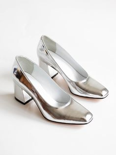"Classic pump in smooth leather with a slightly squared toe and 2 5/8"" block heel. Slips on. Fits true to size. Made in Turkey. Color: Silver Metallic Sizing: American"