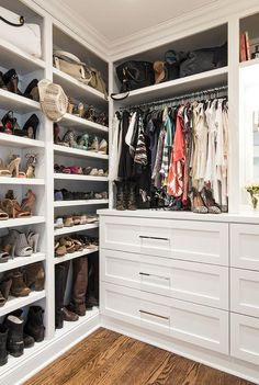Chic walk-in closet features floor to ceiling built-in shoe shelves filled with designer shoes and bags.