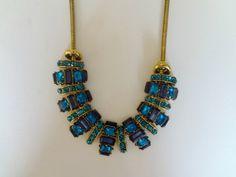 Colar tipo maxicolar curto em bijuteria dourada com pingentes com chatons azuis. R$ 48,44