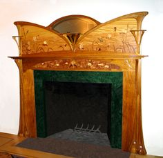 """""""Art Nouveau mantle is hand carved in butternut, with a wide range of exotic woods and veneers in the inlay and marquetry. This design was inspired by the flowing lines of Art Nouveau period furniture…"""""""