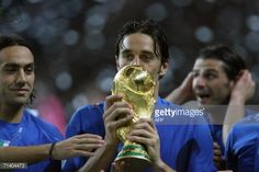 Italian defender Alessandro Nesta Italian forward Luca Toni and Italian forward Vincenzo Iaquinta celebrate with the trophy after the World Cup 2006...