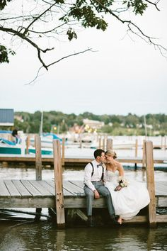 The bride and groom sit on the dock after their waterfront ceremony at a New Hampshire wedding venue. | The Wolfeboro Inn in Wolfeboro, NH