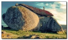 """This real-life Flintstones house stands in Nas Montanhas de Fafe, Portugal. It was built in 1974 and used as a family's rural retreat. Even though the house is next to several immense wind turbines, it still has no running water or electricity. Instead, all of their appliances have been replaced by repurposed animals that spout smarmy one-liners like """"it's a living"""" when in use."""