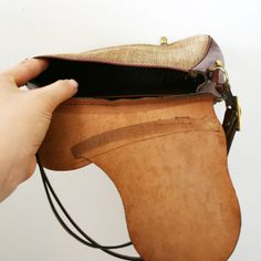 This wonderful leather and tweed handbag has an equestrian style front which looks like a saddle. There is a single internal pocket . The front closure