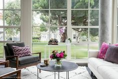 Office space with a large white shag rug, a white sofa, and gray armchairs