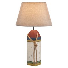 Featuring a buoy-inspired wood base and flaring shade, this charming table lamp illuminates your favorite reading nook or living room in nautical style.