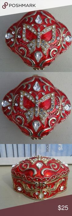 Beautiful vintage Roman Inc. Crystal trinket box Beautiful vintage Roman Inc crystal trinket box made of red with clear crystals with a buttwrfly on top. It is green velvet inside and on mint condition. Never been used, since 2002! Roman, Inc. Jewelry