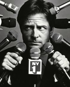 Michael J. Fox // I don't know when this was taken, but it's a GREAT photo of MJFox. He ended up with the Parkinson Poster, & has done good for the serious cause. THe mic's, to ME... represent the difficulty of talking about... telling... and living with a disease you'd rather keep under wraps as long as you can, so you can keep going, living, working -- existing without all the QUESTIONS.
