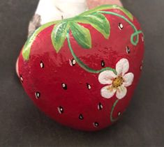 """Beautiful little strawberry with flower. This gem is a rich red with nice detail. Looks great on display, or in the garden or flowerbed! This piece is painted to order so size and shape may vary slightly. Approximate size is 2.25"""" x 2.25"""". Painted rocks are fun, unique pieces of art"""
