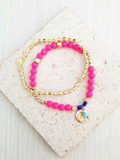 Bead Bracelets, Hot Pink Bracelets, Hot Pink Bead Bracelets, Neon Pink Bracelets, Neon Pink Bracelet Sets, Boho Bracelet Sets, Neon Bracelets  These are a set of two neon pink beaded bohemian bracelets. One bracelet features neon pink colored beads with a small brass coin charm and another bracelet is with gold/neon yellow beads. Its super stretch so size is adjustable. This bracelets looks great with any other layering bracelets or by itself!!!  Measurement:  Bracelet Circumference: 7 3/4…