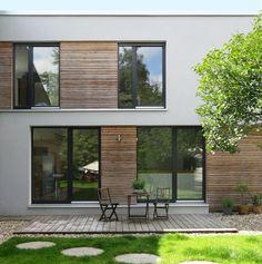 Das Haus wurde 1979 zweigeschossig mit Flachdach als Doppelhaus errichtet. Für die Sanierung wurde die komplette Fassade entfernt und neu gestaltet. Das Haus wirkt nun wie ein grau geputzter Würfel…