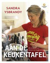 Aan de keukentafel. TV-kok Sandra Ysbrandy geeft tips hoe je van elke maaltijd iets speciaals kan maken. Van snelle gerechten voor doordeweeks tot een avond lang tafelen met vrienden, van ouderwetse appeltaart tot feestelijke hapjes en van een zomerse barbecue tot een goed gevulde picknickmand.     http://www.bruna.nl/boeken/aan-de-keukentafel-9789048817306