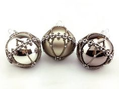 Shiny dark silver bauble with silver filigree pattern. (colour number: 112-502) This is an original pattern by Sine Hummel. Our baubles are made from real glass, and will add an elegant air to your tree or decorations. The beads give them a hint of antique or vintage. The baubles