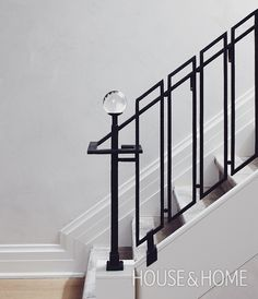 In his Toronto rowhouse, interior designer Jeffrey Douglas dreamt up a graphic wrought-iron railing with a glam glass finial that makes a statement, but still works perfectly with the home's modern take on classic style. | Photographer: Michael Graydon Designer: Jeffrey Douglas
