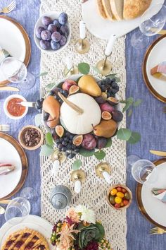 A beautiful tablescape with rich fall colors featuring a centerpiece of fall fruits: Plums, pears, figs, and grapes surround a simple white pumpkin.