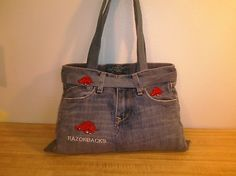 "I made this bag from a pair of Old Navy Blue Jeans and embroidered Razorbacks on front.  On back of one pocket is embroidered ""Go Hogs Go"" and the other pocket a Razorback.  The belt added also has a Razorback embroidered on it.  The jeans were a medium to light blue with the faded look.  The bag measures approximately 14"" across the top and 16"" at the bottom.  The sides measure is approximately 11 1/2"".  Can be carried by the handles or used as a should bag. $3.95 S/H bag $14.99."