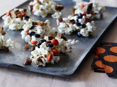 Halloween Popcorn Treats : These aren't ordinary popcorn balls. Giada's sticky treats contain chopped chocolate bars, chocolate chip cookies, salted almonds and Halloween-colored candies. via Food Network Halloween Desserts, Halloween Popcorn, Halloween Party Treats, Halloween Foods, Halloween Fun, Halloween Recipe, Spooky Treats, Halloween Decorations, Fall Treats