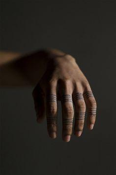 Pequeños tatuajes de lineas en los dedos.