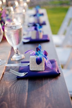 """Beautiful farm tables with """"The Color Purple"""". Purple linen napkins and Wedding Favors with blue dyed dendrobium orchids. By Bliss Wedding Design & Spectacular Events"""