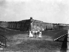 """GOLF: """"On the golf links,"""" Saint Augustine, Florida, 1902. The fortress in the background, the Castillo de San Marcos, is the oldest masonry fort built in the current United States. The two couples are most likely vacationing in the area."""