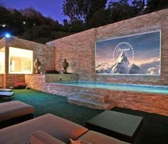 A very ostentatious backyard movie theater/pool combo!!.