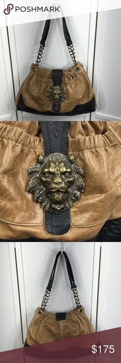 """Leatherock Fierce Lion Bag NWOT OOAK. Distressed tan and beautifully textured black leather. 17 1/2"""" wide at base and 11 1/2"""" tall. Bag opens to 11"""" wide at top. Leather interior w/1 zip and 1 slide-in pocket. 2 exterior pockets. Snaps at sides allow for width adjustment. Beautifully detailed lion head closure (brass & Swarovski). Heavy aged brass chain and leather straps give a 12 1/2"""" drop. Comes with dust bag. New, never used. Perfect condition. A substantial bag that should be used when…"""