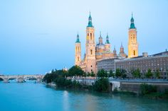 "Best Cities to Visit in Spain. Situated on the Ebro River, Zaragoza is a large and bustling city and the capital of Aragon. With a history that stretches back to 25 B.C., the city boasts architectural attractions from every era, from still-standing remnants of Roman walls to the Moorish castle Aljaferia, which Giuseppe Verdi used as his setting for the opera ""The Troubadour."" Of the city's two magnificent cathedrals, the Cathedral of Our Lady of the Pillar attracts the most visitors."