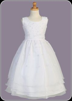 This white Communion dress is highlighted by a garden of petite embroidered flowers with pearl centers. The sleeveless bodice, thick organza sash and t-length skirt with three layers of organza result in a beautiful look that is sure to please.