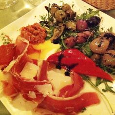 Italian antipasti with ham bone, grilled peperoni and onions, green olives and balsamic vinegard