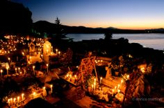 Day of the Dead, Janitzio island. During prehispanic times Patzcuaro's lake was thought to be an important entrance to the underworld. During that day, its doors open, and the souls of the departed return to earth to visit their family and friends. At night in the small graveyard on Janitzio Island, illuminated only by a sea of candles, Purépechas women speak quietly with beloved departed souls at graves adorned with offerings of food, candies, liquor, or whatever their dead enjoyed while…
