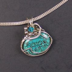 """Turquoise Sea Sterling Silver and Turquoise Wire Wrapped Pendant   Oval turquoise cab and sterling silver wire wrapped pendant accented with sterling silver beads and a teal Swarovski crystal. The chain is for display only and not included.   Pendant measures 1 1/8"""" long by 1"""" wide.  One of a kind.  Price: $40"""