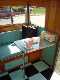 Vintage camper with a side table  Love the black & aqua flooring.