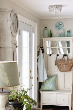 How to style an mud room hall tree from HomeGoods for the spring and summer is an easy one! We love the look of a straw market basket hanging from one of the hooks. A pretty pillow and collection of old blue bottles spells out the seasonal change making your entry look light and breezy. Sponsored by HomeGoods.