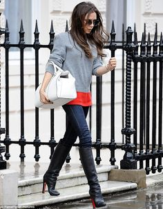 Victoria Beckham in a grey jumper, and skinny jeans from her label, with Christian Louboutin boots.. white handbag, and sunglasses also from her collection - less is more in accessorizing!!