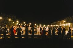 A glorious outdoor wedding surrounded by festoon lighting. || Melissa Mills Photography