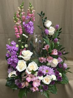 boutique- pink snapdragons, purple stock, white standard roses, pink alstromeria, purple chrysanthemum daisies, white button mum daisies, purple tulips, Italian ruscus, leather fern and salal fresh flowers in a urn design for a funeral